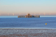 Derelict pier and windfarm Stock Images