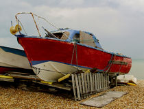 A derelict red motor boat on a beach Royalty Free Stock Photos