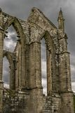A ruin of an abbey from a bygone age. A derelict ruin of a church, abbey, monastery or convent. large open archways. arched windows. rain clouds gathering in stock photo