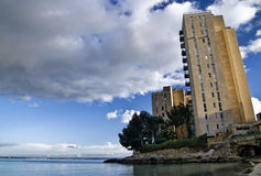 Derelict tower block by sea Stock Images