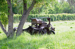 Derelict tractor in field. Derelict tractor under tree in countryside field Royalty Free Stock Photography