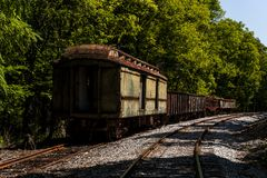 Derelict Train Cars - Abandoned Railroad in Kentucky. Derelict train cars, including one used for mail, remain on a then-abandoned railroad track between stock photography