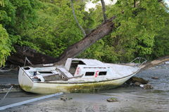 Derelict yacht. Deserted yacht washed on beach Stock Image