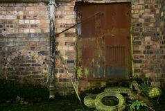 Dereliction. Derelict old factory with rusty doors, crumbling bricks and moss royalty free stock image