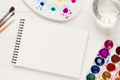 Derida su con gli strumenti artistici sulla tavola bianca Fotografia Stock