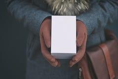 Derida su con la scatola bianca da uno smartphone La ragazza in un cappotto e nei guanti marroni tiene un regalo in sue mani fotografia stock