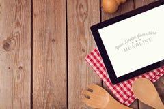 Derida sul modello con la compressa per la ricetta, il menu o la cottura dell'esposizione di app Immagine Stock
