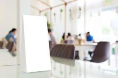 Derida sulla struttura in bianco del menu del modello in ristorante con il BAC vago Immagine Stock
