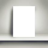 Derisione bianca in bianco del manifesto su sullo scaffale bianco fotografia stock libera da diritti