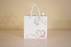 Derisione in bianco della borsa del regalo del Libro Bianco su che sta su una tavola di legno E Fotografia Stock