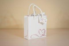 Derisione in bianco della borsa del regalo del Libro Bianco su che sta su una tavola di legno E Fotografie Stock Libere da Diritti