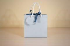 Derisione in bianco della borsa del regalo della carta blu su che sta su una tavola di legno em Immagine Stock