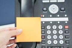 Derisione dell'attaccatura della donna sulla nota appiccicosa sul telefono del IP Fotografia Stock Libera da Diritti