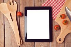 Derisione della compressa di Digital sul modello con gli utensili da cucina ed i pomodori Vista da sopra fotografia stock