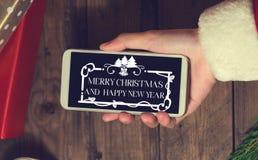 Derisione dello Smart Phone di uso di Santa su con un copyspace per il Natale Chr Fotografia Stock Libera da Diritti
