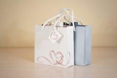 Derisione di carta della borsa del regalo dello spazio in bianco due su che sta su una tavola di legno Emp Fotografia Stock