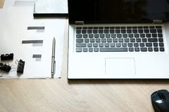Derisione di identità corporativa su su uno scrittorio con il computer portatile e sulla documentazione con i grafici fotografie stock libere da diritti