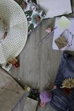 Derisione su area di lavoro con il cappello, la penna, i jeans, la carta, il pendente, le coperture, i fiori, il giocattolo ed il immagini stock libere da diritti