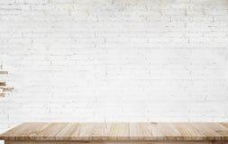 Derisione sulla tavola di legno con il muro di mattoni bianco Fotografia Stock