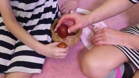 Derivato e madre che si siedono sul letto e che combattono con le uova di Pasqua video d archivio