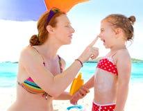 Derivato e madre in spiaggia con protezione solare Immagine Stock Libera da Diritti