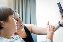 Derivato e sua madre che fanno un selfie facendo uso dello Smart Phone e del sorridere immagini stock