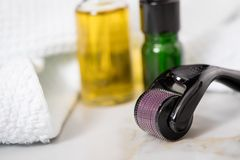 Derma roller, towel, yellow cosmetic oil and green serum dropper bottles for anti ageing lifting or acne treatment on marble. Derma roller, towel, yellow royalty free stock images