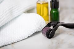 Derma roller, towel, yellow cosmetic oil and green serum dropper bottles for anti ageing lifting or acne treatment on marble. Derma roller, towel, yellow royalty free stock photos