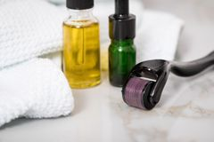 Derma roller, towel, yellow cosmetic oil and green serum dropper bottles for anti ageing lifting or acne treatment on marble. Derma roller, towel, yellow stock photos