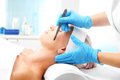 Dermabrasion manual using a surgical blade. Royalty Free Stock Photography