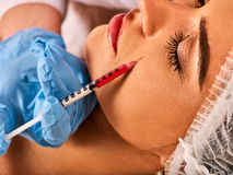 Dermal fillers lips of woman in spa salon with beautician. Stock Image