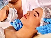 Dermal utfyllnadsgods av kvinnan i brunnsortsalong med kosmetologen royaltyfria foton