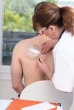 Dermatólogo que examina la piel de un paciente fotos de archivo
