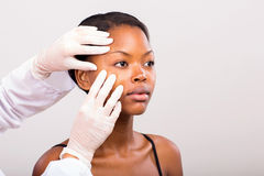 Dermatologist checking skin Stock Photos