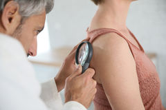 Dermatologist examining the mole. Dermatologist looking at woman's mole with magnifier Stock Images
