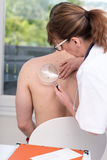 Dermatologist examining the skin of a patient. Dermatologist examining the skin on the back of a patient Stock Photos