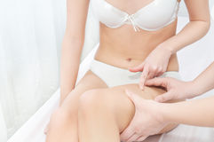 Dermatologist inspecting woman patients skin. Dermatologist inspecting women patients skin looking for cellulite Royalty Free Stock Photos