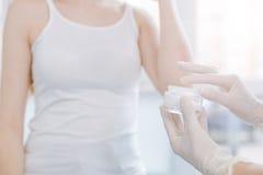 Dermatologo abile che applica crema medica su pelle paziente sul lavoro Fotografia Stock