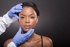 Dermatologo che controlla donna Fotografie Stock