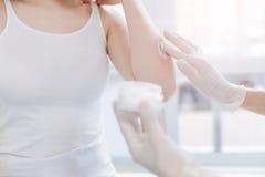 Dermatologo professionista che mette crema medica sulla pelle paziente sul lavoro Immagine Stock Libera da Diritti