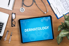 DERMATOLOGY. Professional doctor use computer and medical equipment all around, desktop top view Royalty Free Stock Photos