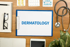 DERMATOLOGY. Professional doctor use computer and medical equipment all around, desktop top view royalty free stock photography