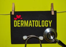 DERMATOLOGY on top of yellow background. A stethoscope and blackboard with word DERMATOLOGY on top of yellow background. Medical, health and education concepts stock photography