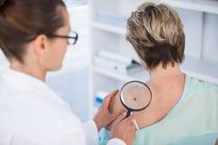 Dermatoloog die mol van vrouwelijke patiënt met vergrootglas onderzoeken royalty-vrije stock afbeelding