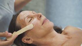 Dermatoloog die verjongend masker op teruggetrokken vrouwelijk gezicht van toepassing zijn stock footage