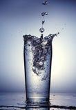 Derramamento da agua potável em um vidro claro. Imagem de Stock