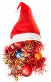 Derramamento das decorações do Natal sobre o chapéu vermelho de Santa Fotografia de Stock