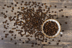 Derramamento do copo de café a tabela de madeira dos feijões um fundo escuro Desenho azul Fotografia de Stock Royalty Free