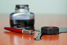 Derramamento preto da tinta perto da pena vermelha na tabela Imagens de Stock Royalty Free