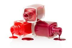 Derramamento vermelho das garrafas do verniz para as unhas Foto de Stock Royalty Free